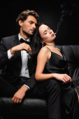 seductive woman with closed eyes leaning on elegant man holding lighter isolated on black