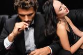 csábító barna nő csukott szemmel támaszkodik elegáns férfi dohányzás cigaretta elszigetelt fekete