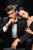 érzéki nő csukott szemmel ölelés váll elegáns férfi dohányzik, és nézi kamera elszigetelt fekete