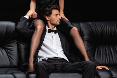 Young man in suit holding hand of seductive woman sitting above him on couch isolated on black stock vector
