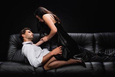 Passionate elegant woman seducing man lying on leather sofa isolated on black stock vector