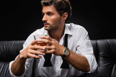 Young man in untied tie and white shirt looking away while holding glass of whiskey isolated on black stock vector