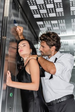 Elegant man touching neck of sexy woman while seducing her in elevator stock vector