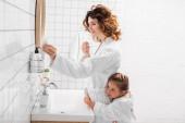 Usmívající se žena se zubní pastou v blízkosti dítěte v koupelně