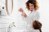 Žena v županu drží kosmetické sérum v blízkosti dítěte v koupelně