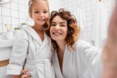 Usmívající se matka objímající dítě a při pohledu na kameru v koupelně