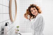 Usmívající se žena s rukama v blízkosti vlasů při pohledu do kamery v blízkosti toaletní potřeby na rozmazané popředí