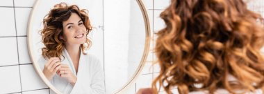 Curly woman looking at mirror on blurred foreground in bathroom, banner stock vector