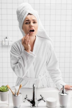 Worried woman in towel and bathrobe touching chin stock vector