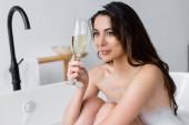 Bruneta žena s pěnou na vlasech drží sklenici šampaňského ve vaně