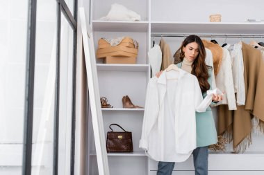 Confused woman holding hanger with shirt in wardrobe