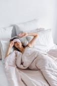 Barna nő tartja bekötött szemmel az ágyon otthon