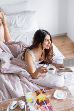 Smiling woman relaxing with coffee and book on bed stock vector