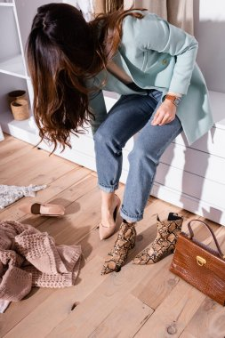 Young woman wearing heeled shoe near clothes and handbag in wardrobe