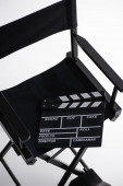 high angle view of clapperboard on director chair on white, cinema concept