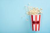Draufsicht auf gestreiften Kartoneimer mit Popcorn auf blau, Kinokonzept