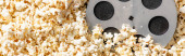 top view of film bobbin on airy delicious popcorn, banner, cinema concept
