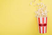 Draufsicht auf gestreiften Eimer mit knusprigem Popcorn auf gelb, Kinokonzept