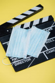 clapperboard and medical masks on yellow, cinema concept