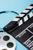 close up view of film reel and clapperboard on blue, cinema concept