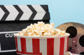 close up view of bucket with popcorn near clapperboard and film reel isolated on blue, cinema concept