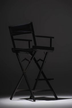 Black director chair on dark grey background, cinema concept stock vector