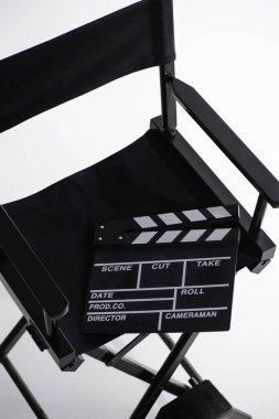 High angle view of clapperboard on director chair on white, cinema concept stock vector