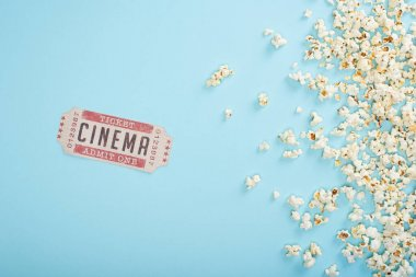 Top view of cinema ticket near scattered popcorn on blue stock vector