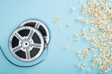 Top view of film reels near scattered popcorn on blue, cinema concept stock vector