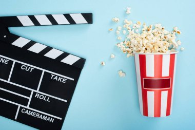 Top view of striped bucket with popcorn near clapperboard on blue, cinema concept stock vector