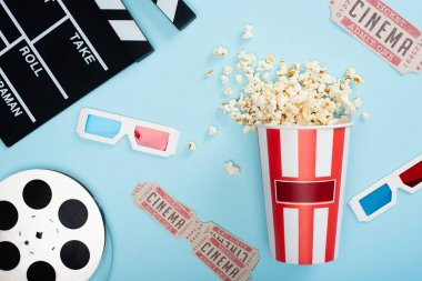 Top view of clapperboard, 3d glasses, cinema tickets, film reel and bucket of popcorn on blue stock vector