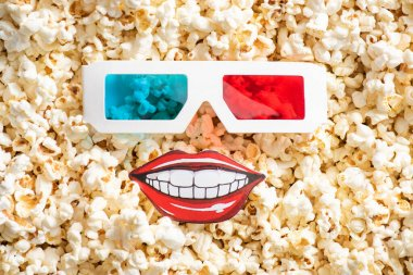 Top view of 3d glasses and paper cut smiling mouth on crispy popcorn, cinema concept stock vector