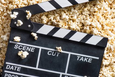 Top view of clapperboard on salty popcorn, cinema concept stock vector