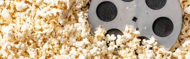 Top view of film bobbin on airy delicious popcorn, banner, cinema concept stock vector