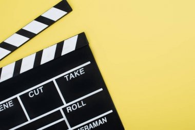 Top view of clapperboard on yellow background with copy space, cinema concept stock vector