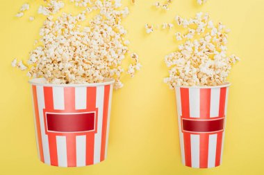 Top view of big and small buckets with tasty popcorn on yellow, cinema concept stock vector