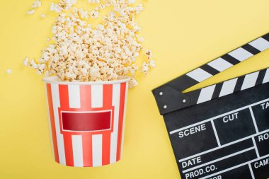 Top view of bucket with tasty popcorn near clapperboard on yellow, cinema concept stock vector