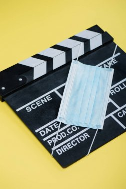 Medical mask and clapper board on yellow, cinema concept stock vector