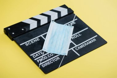 Medical mask on clapperboard on yellow, cinema concept stock vector