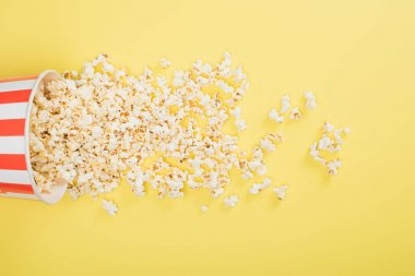 Top view of paper bucket and scattered popcorn on yellow, cinema concept stock vector
