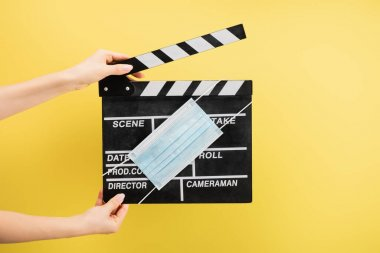Cropped view of camera assistant with clapperboard and medical mask isolated on yellow, cinema concept stock vector