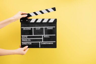 Partial view of camera assistant holding clapperboard isolated on yellow, cinema concept stock vector