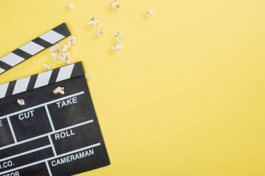 Top view of clapperboard near scattered popcorn on yellow, cinema concept stock vector