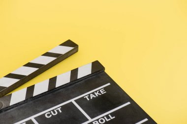 Close up view of clapperboard on yellow background, cinema concept stock vector