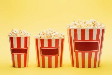 Big, medium and small buckets of popcorn on yellow, cinema concept stock vector