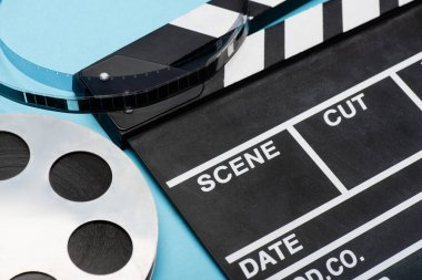 Close up view of clapperboard and film bobbin on blue, cinema concept stock vector