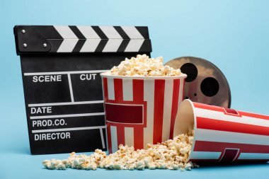 Clapperboard, film reel and buckets with popcorn on blue, cinema concept stock vector