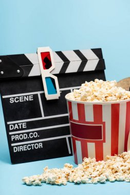 Clapperboard, 3d glasses and bucket with tasty popcorn on blue, cinema concept stock vector