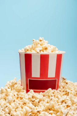 Striped bucket and pile of tasty popcorn isolated on blue, cinema concept stock vector