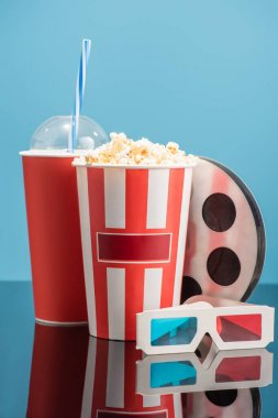 Cup of soda, bucket with popcorn, 3d glasses and film bobbin on glossy surface isolated on blue, cinema concept stock vector